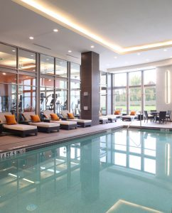 View of The Hotel Pool with lounge chairs and view into fitness room at Arundel Preserve