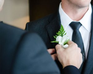 Groom with groomsman placing boutonniere on before the wedding at our Arundel Preserve hotel