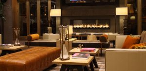 The Hotel Lobby lounge area with large glass fireplace with various chairs and couches and lamps in Hanover MD