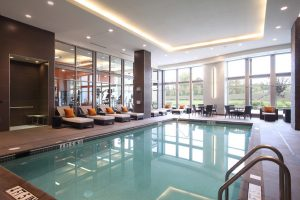 Arundel Mills Hotel Pool with lounge chairs on one side by the windows of the Fitness Center looking in.