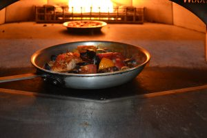 A plate of seafood cooking in the brick fire over at the Vivo Italian Kitchen in Hanover, Maryland