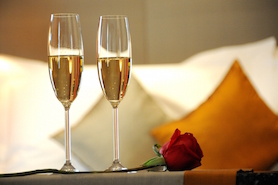 Two glasses of wine sitting on a bed with a rose at the Hotel at the Arundel Preserve
