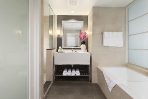 Beautiful light bath with tile floor tub, & single person sink with flower vase & towels at our Arundel Mills Hotel
