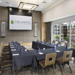 A small but spacious meeting room featuring a projector, a u shaped table and more at the Hotel at Arundel Mills