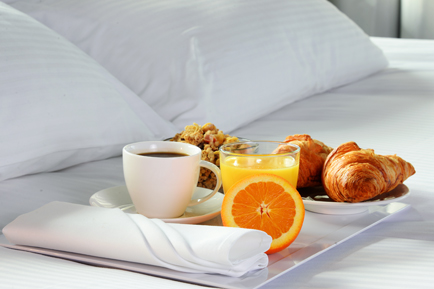 A tray of orange juice, granola, crescents & more on a bed at the Arundel Preserve Hotel