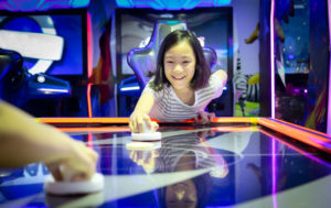 little girl playing arcade game