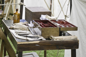 Instrument table in surgeons's tent, with bottle of chloroform and amputation saw, at reenactment of American Civil War