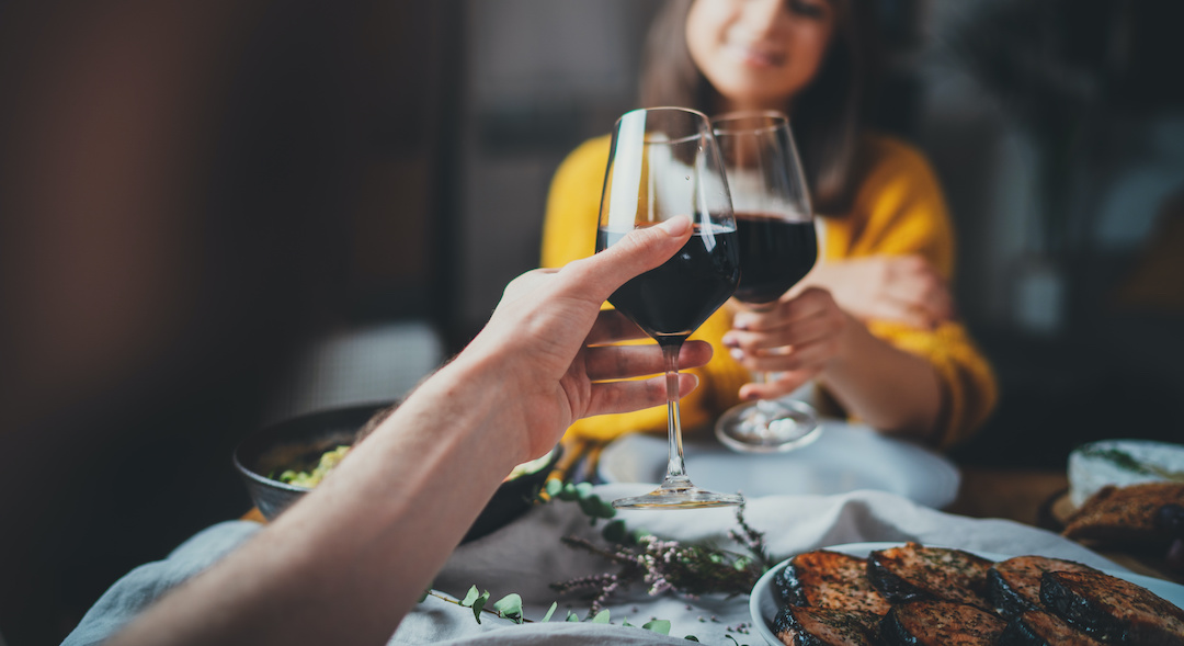 romantic couple making cheers with glasses of red wine during date in restaurant